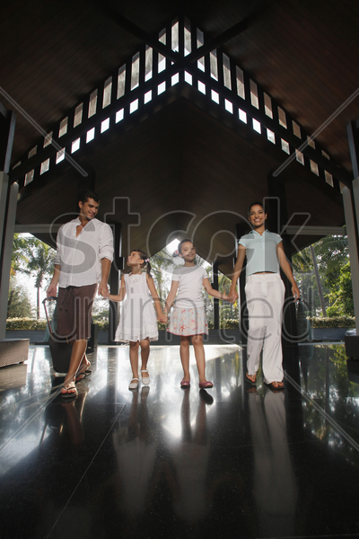 family walking into resort while holding hands stock photo