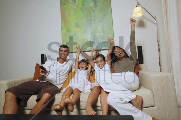 family watching tv together, girls and woman cheering stock photo