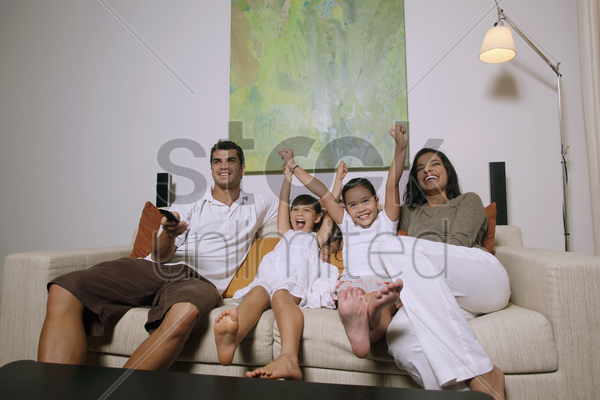 family watching tv together, girls cheering with arms raised stock photo