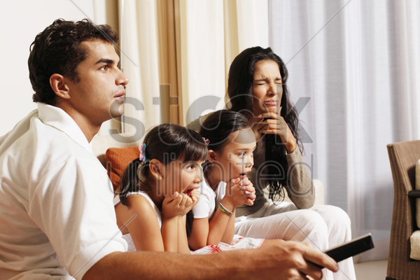 family watching tv together stock photo