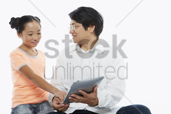 father and daughter using a digital tablet together stock photo