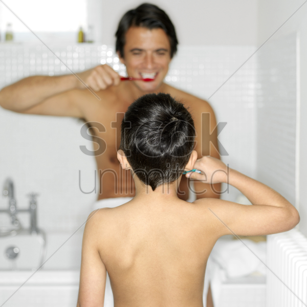 father and son brushing teeth together stock photo