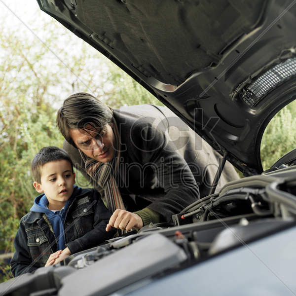 father and son checking the condition of their car stock photo