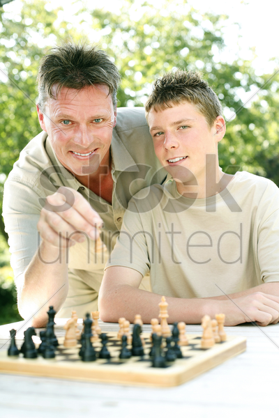 father and son playing chess game stock photo