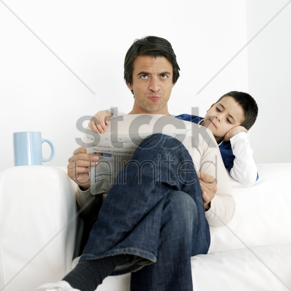 father and son reading newspaper stock photo