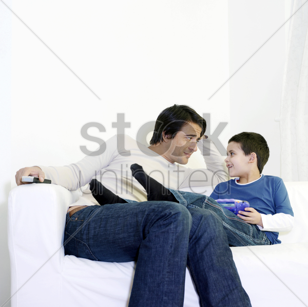 father and son sitting on the couch chatting stock photo