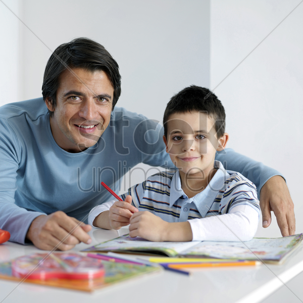 father and son smiling at the camera stock photo