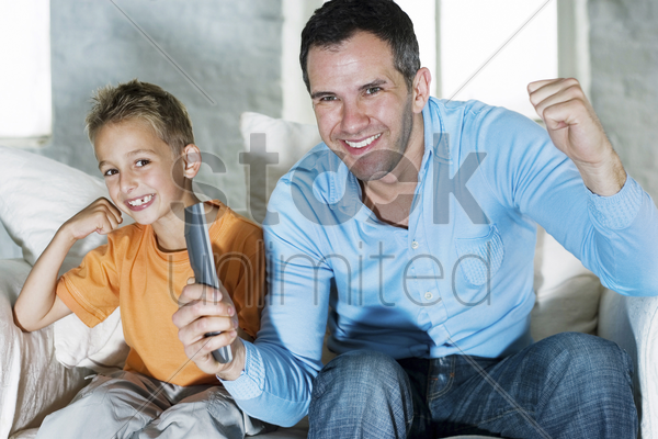 father and son watching television together stock photo