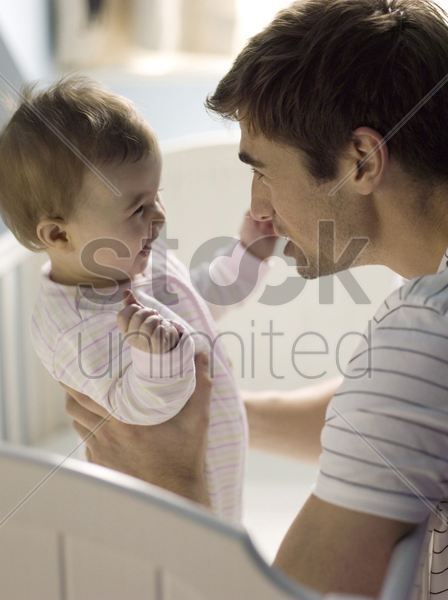 father carrying baby girl from the crib stock photo