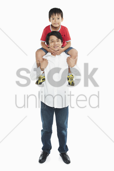 father carrying son on his shoulders stock photo