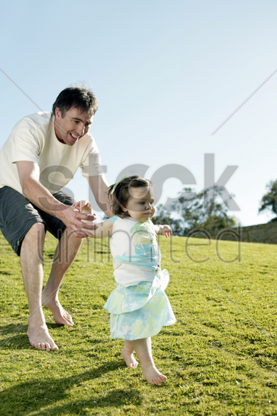 father chasing after his daughter stock photo
