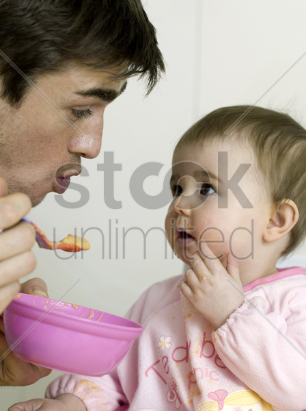 father feeding baby girl stock photo