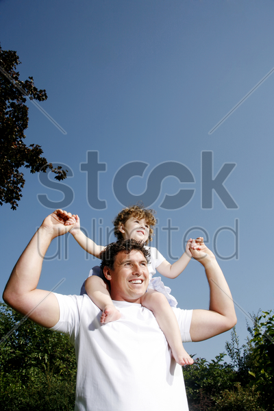 father giving daughter a piggy back ride stock photo