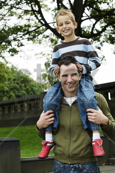 father giving son a piggy back ride stock photo