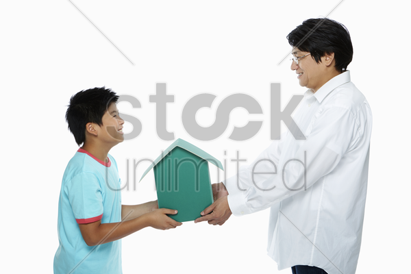 father handing over a cardboard house to his son stock photo