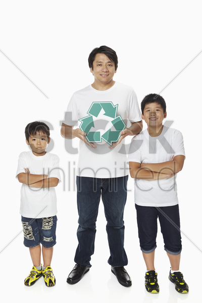 father holding up a recycle logo while sons stand with arms crossed stock photo