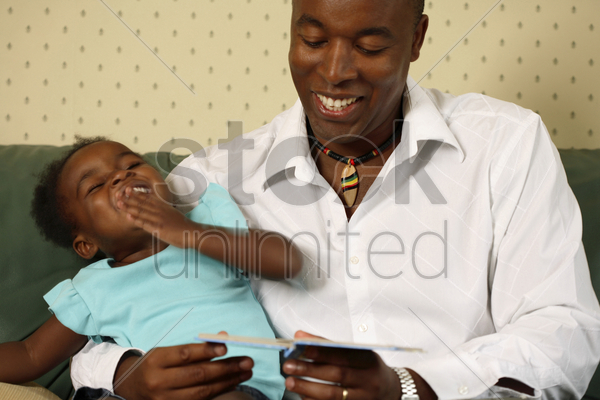 father reading for his daughter stock photo