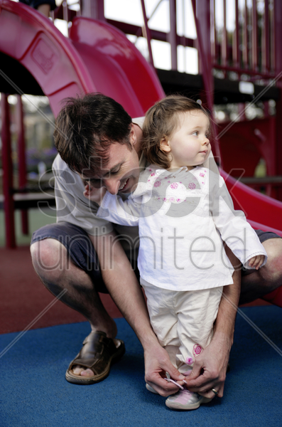 father tying shoelace for her daughter stock photo