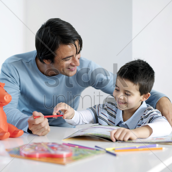 father watching son doing homework stock photo
