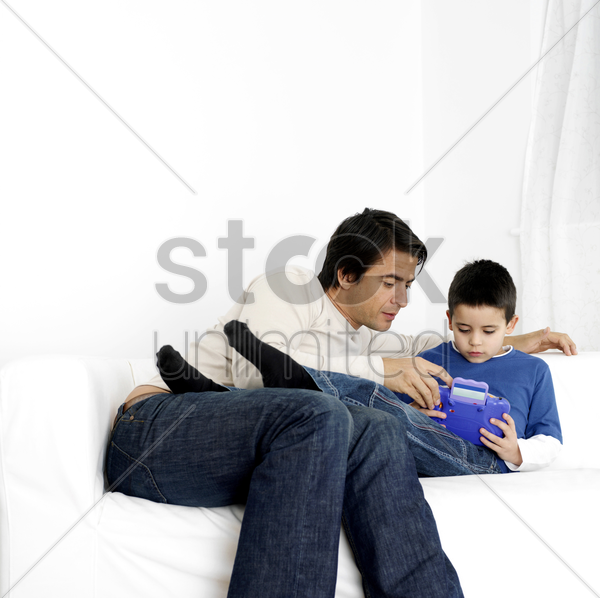 father watching son playing with toy stock photo