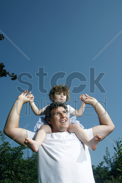 father with daughter on his shoulder stock photo