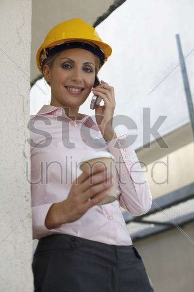 female architect holding a cup of coffee while talking on the phone stock photo