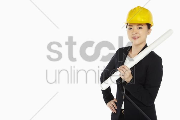 female architect holding up a construction plan stock photo