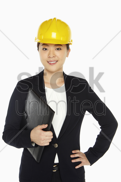 female architect smiling and holding a folder stock photo