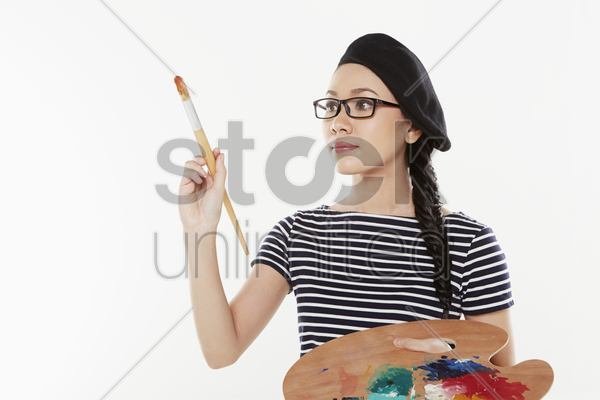 female artist holding a paint brush and palette stock photo