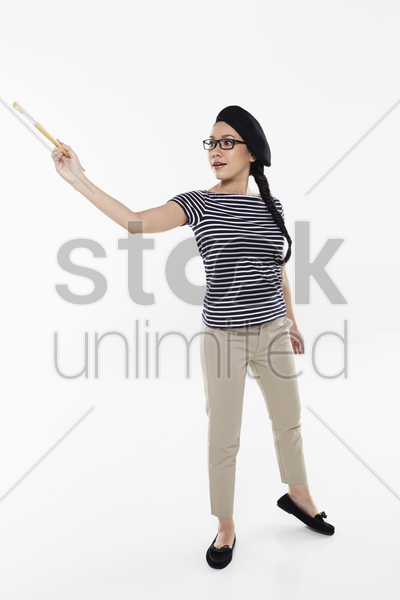 female artist holding a paint brush stock photo