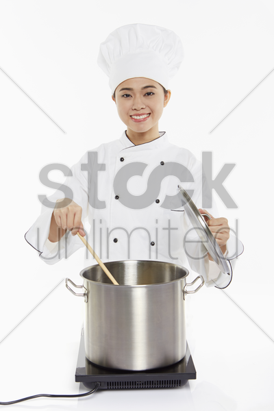 female chef cooking and stirring stock photo