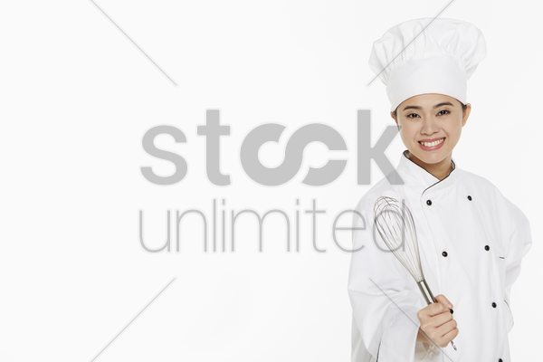female chef holding a wire whisk stock photo