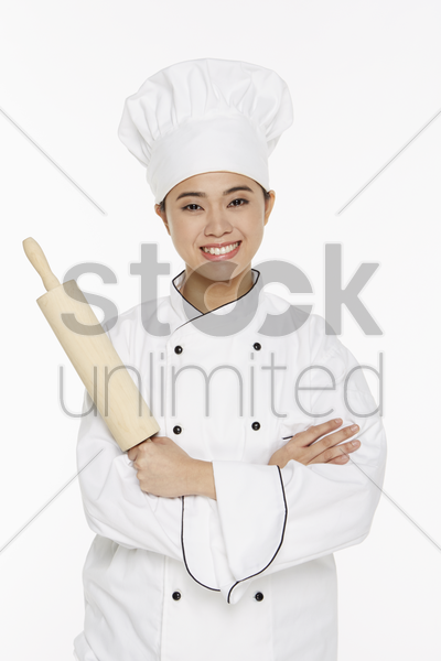 female chef holding up a rolling pin stock photo