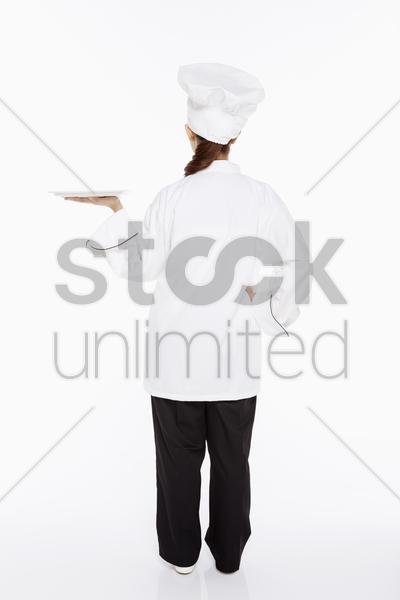 female chef holding up a tray stock photo