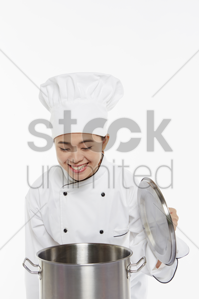 female chef smelling food from the pot stock photo
