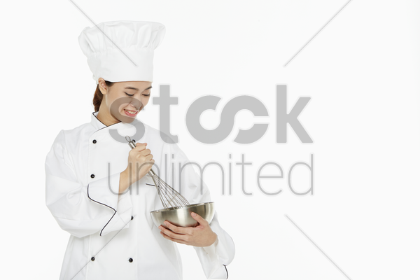 female chef using a wire whisk stock photo