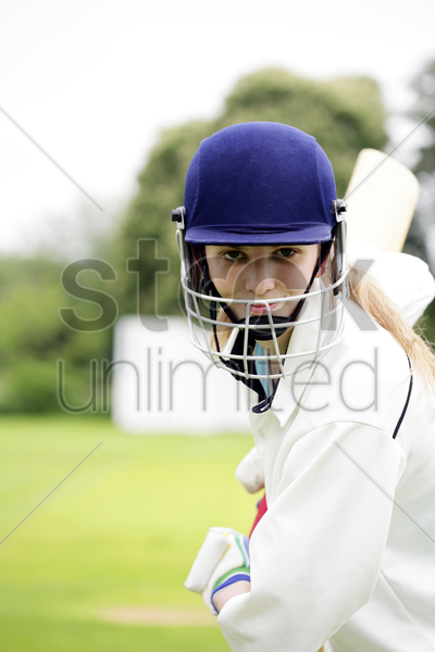 female cricket player holding a cricket bat stock photo