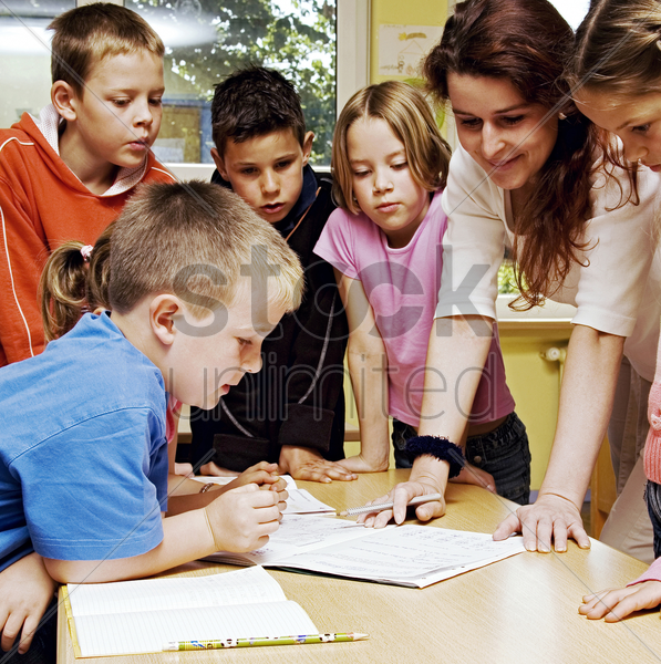 female teacher looking at a book with her students surrounding her stock photo