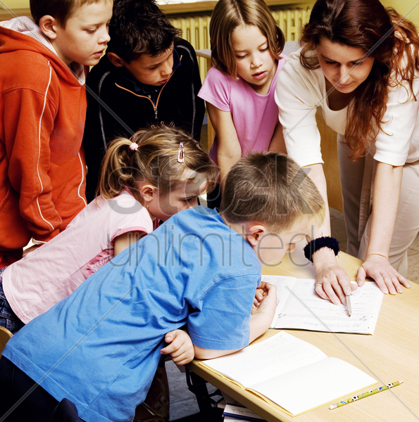 female teacher pointing at a book with students surrounding her stock photo