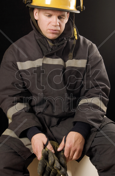 fire fighter holding protective gloves stock photo