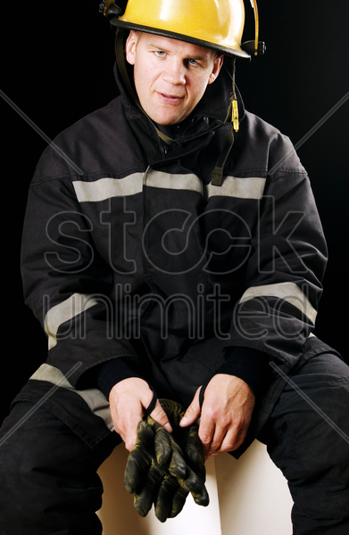 fireman holding black gloves stock photo