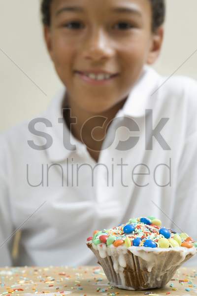 focus on a cupcake with boy sitting in the background stock photo