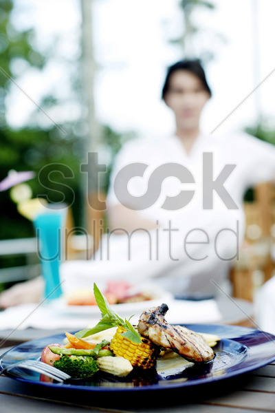 focus on a mouth-watering meal with a man sitting in the background stock photo