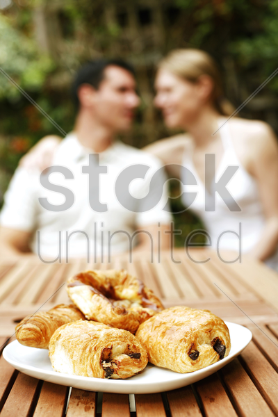 focus on a plate of croissants with couple sitting in the background stock photo