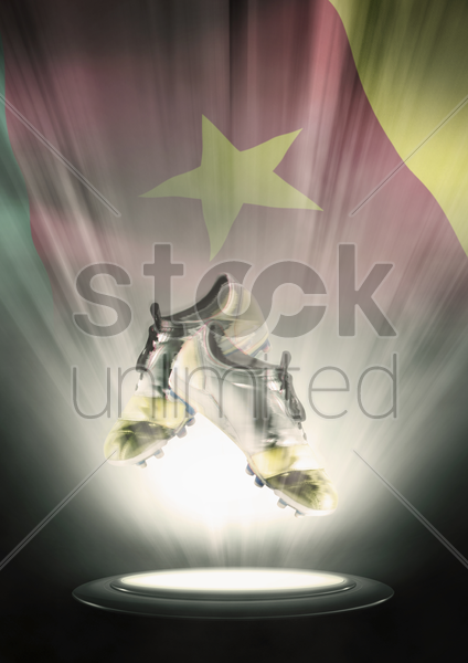 football cleats with cameroon flag backdrop stock photo