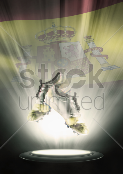 football cleats with spain flag backdrop stock photo