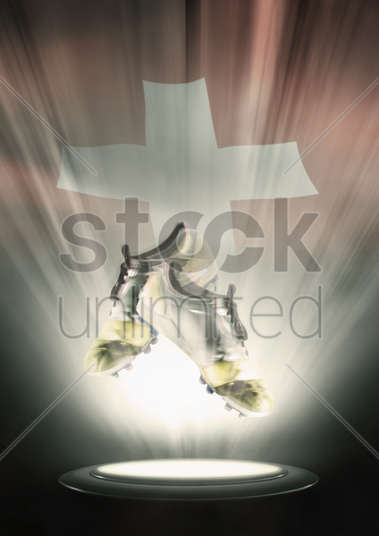 football cleats with switzerland flag backdrop stock photo