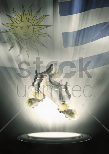 football cleats with uruguay flag backdrop stock photo