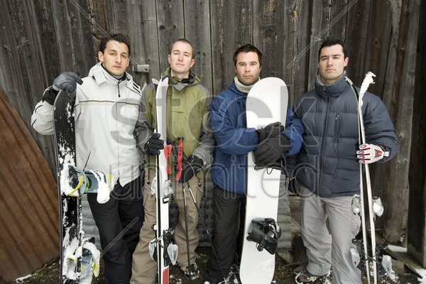four men in winter clothing holding snowboard stock photo