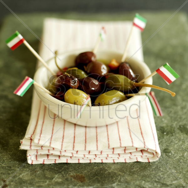 fresh italian olives in a small ceramic bowl with italian flag picks sitting on a red stripy napkin stock photo